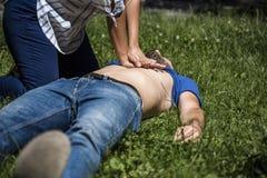 Ragazza che fa rianimazione cardiopolmonare ad un tipo incosciente dopo l'attacco di cuore fotografia stock libera da diritti