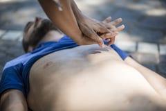 Ragazza che fa rianimazione cardiopolmonare ad un tipo incosciente dopo l'attacco di cuore fotografie stock