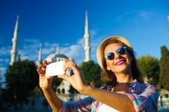 Ragazza che fa selfie dallo smartphone sui precedenti del Bl Immagine Stock