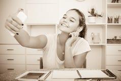 Ragazza che fa selfie durante lo studio Fotografia Stock
