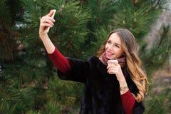 Ragazza che fa selfie nel parco di autunno, donna attraente che cammina nel parco nel giorno di autunno immagine stock libera da diritti
