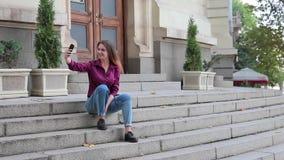 Ragazza che fa selfie su un telefono cellulare che si siede sui punti all'aperto video d archivio