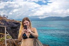 Ragazza che fa selfie sul fondo del mare dall'alta scogliera Fotografia Stock