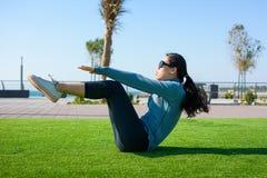 Ragazza che fa situps sull'erba, allenamento all'aperto Immagini Stock