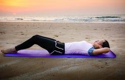 Ragazza che fa situps sulla spiaggia al tramonto Fotografie Stock Libere da Diritti