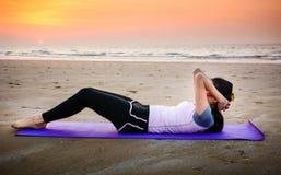 Ragazza che fa situps sulla spiaggia al tramonto Fotografia Stock Libera da Diritti