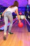 Ragazza che fa tiro della sfera nel randello di bowling Fotografie Stock Libere da Diritti