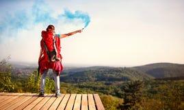 Ragazza che fa un'escursione e che mostra la torcia dei segnali di fumo fotografia stock