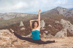Ragazza che fa yoga nel paesaggio delle montagne Fotografia Stock