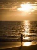 Ragazza che funziona sulla spiaggia al tramonto Fotografia Stock