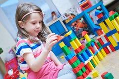 Ragazza che gioca con i blocchetti di legno del giocattolo all'interno fotografia stock
