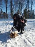 Ragazza che gioca con il cane del husky che si trova sulla neve Fotografia Stock