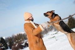 Ragazza che gioca con il cane di salto contro il cielo blu Immagine Stock