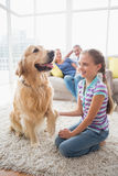 Ragazza che gioca con il cane mentre genitori che si rilassano a casa Fotografie Stock