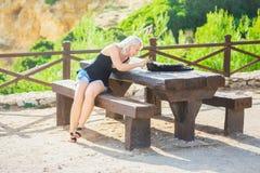Ragazza che gioca con il gatto sulla tavola di picnic fotografie stock libere da diritti