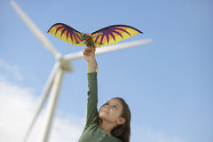 Ragazza che gioca con l'aquilone al parco eolico Fotografia Stock