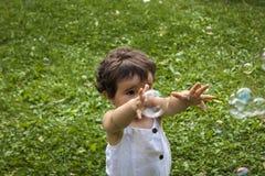 Ragazza che gioca con le bolle di sapone nel giardino Immagini Stock Libere da Diritti