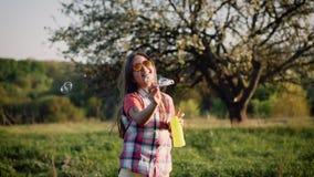 Ragazza che gioca con le sapone-bolle il giorno soleggiato archivi video