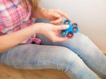 Ragazza che gioca con un giocattolo colourful del filatore di irrequietezza della mano Immagine Stock