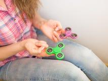 Ragazza che gioca con un giocattolo colourful del filatore di irrequietezza della mano Immagini Stock