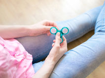 Ragazza che gioca con un giocattolo colourful leggero lucido del filatore di irrequietezza della mano Fotografie Stock