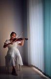 Ragazza che gioca l'indicatore luminoso scuro dello studio del violino nel paese Fotografie Stock Libere da Diritti