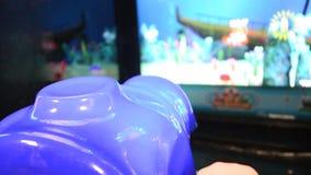 Ragazza che gioca la macchina di videogioco arcade ad un parco di divertimenti video d archivio