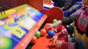 Ragazza che gioca la macchina di videogioco arcade ad un parco di divertimenti archivi video