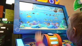 Ragazza che gioca la macchina di videogioco arcade ad un parco di divertimenti stock footage