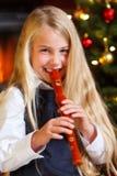 Ragazza che gioca registratore sulla notte di Natale Fotografia Stock