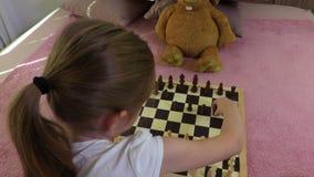Ragazza che gioca scacchi con il giocattolo stock footage