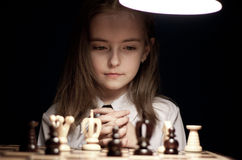 Ragazza che gioca scacchi sotto la lampada Immagine Stock
