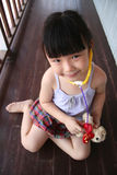 Ragazza che gioca stetoscopio sul cucciolo del giocattolo immagine stock libera da diritti