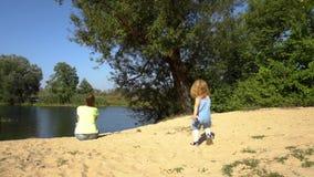 Ragazza che gioca sulla riva vicino alla madre video d archivio