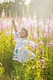 Ragazza che gioca in un campo dei fiori Fotografie Stock Libere da Diritti