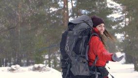 Ragazza che gira intorno sotto la forte nevicata Viaggiatore, ritratto positivo nella foresta di inverno che fa un'escursione, am video d archivio
