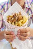 Ragazza che giudica girobussola greca con le fritture vicina su sulla tavola Immagine Stock Libera da Diritti