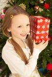 Ragazza che giudica presente davanti all'albero di Natale Fotografia Stock