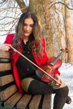 Ragazza che giudica violine in mani Fotografia Stock