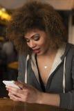 Ragazza che gode della bevanda mentre giocando sul suo telefono Fotografie Stock Libere da Diritti