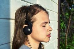 Ragazza che gode della musica all'aperto con le cuffie e uno smartphone fotografie stock