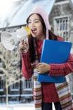 Ragazza che grida con il megafono vicino all'edificio scolastico Fotografie Stock Libere da Diritti