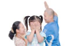 Ragazza che grida con il suo combattimento del genitore nel fondo fotografie stock libere da diritti