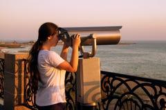 Ragazza che guarda con il binocolo a gettoni sulla riva di mare di Cannes, Francia Fotografie Stock