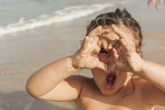 Ragazza che guarda con un tiraggio del cuore con le sue mani Spiaggia fotografie stock