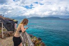 Ragazza che guarda il mare dall'alta scogliera Immagini Stock Libere da Diritti