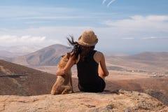 Ragazza che guarda il panorama con il suo cucciolo di cane fotografia stock libera da diritti