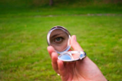 Ragazza che guarda in un piccolo specchio in sua mano Fotografie Stock Libere da Diritti