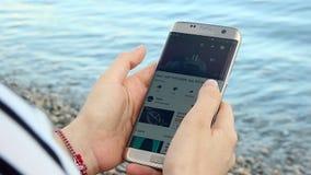 Ragazza che guarda YouTube sul suo Smartphone sulla spiaggia video d archivio