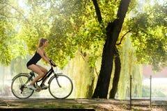 Ragazza che guida una bici Fotografie Stock